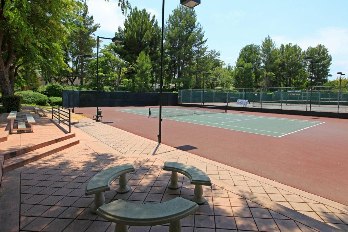 an empty park bench next to a basketball court