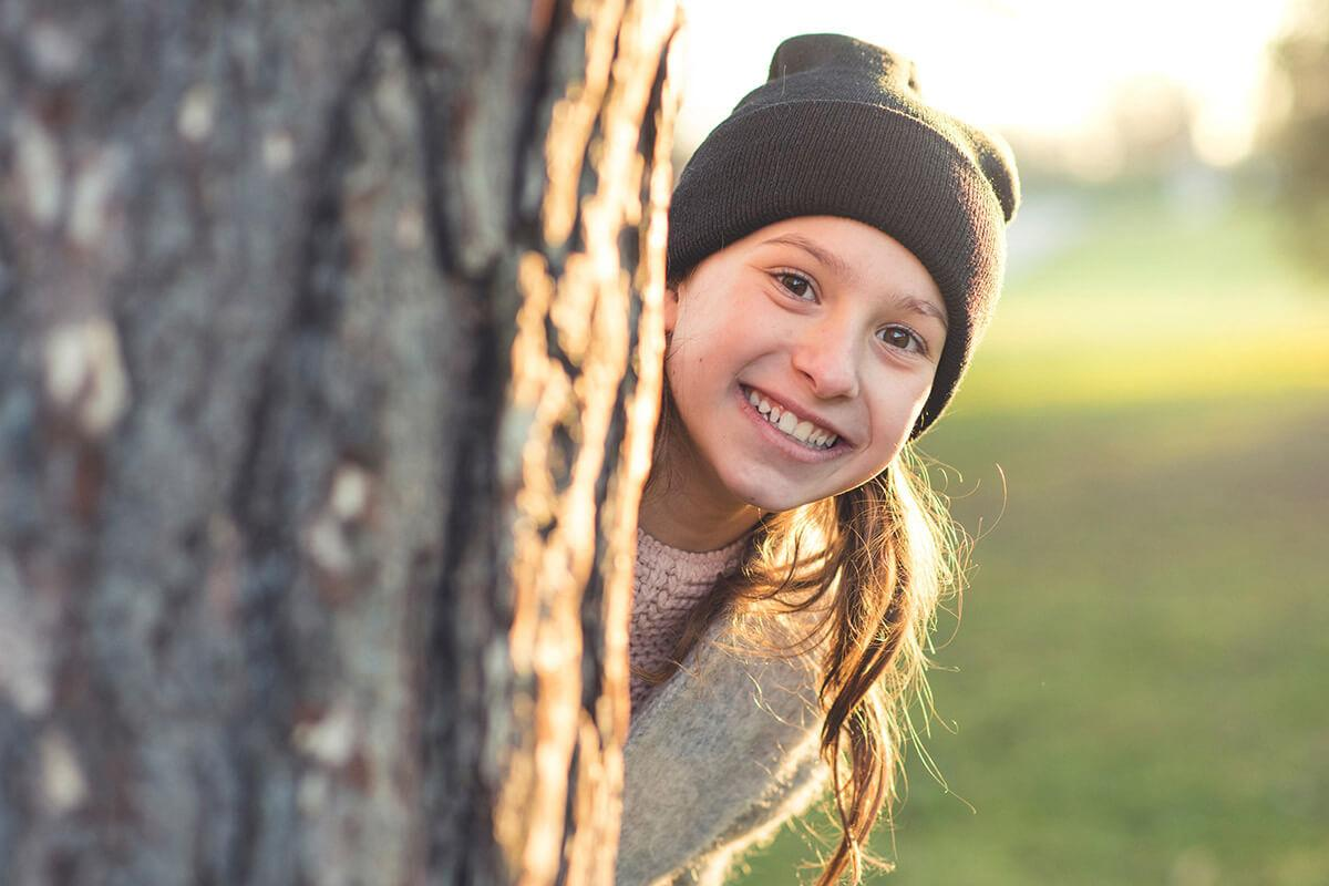 a close up of a girl wearing a hat and smiling at the camera