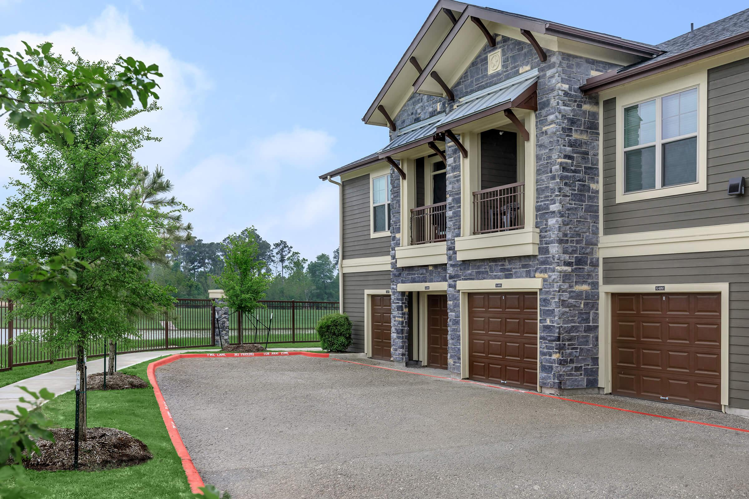 Attached garages at Park at Tour 18 apartments and paved walking trail through the landscaping.