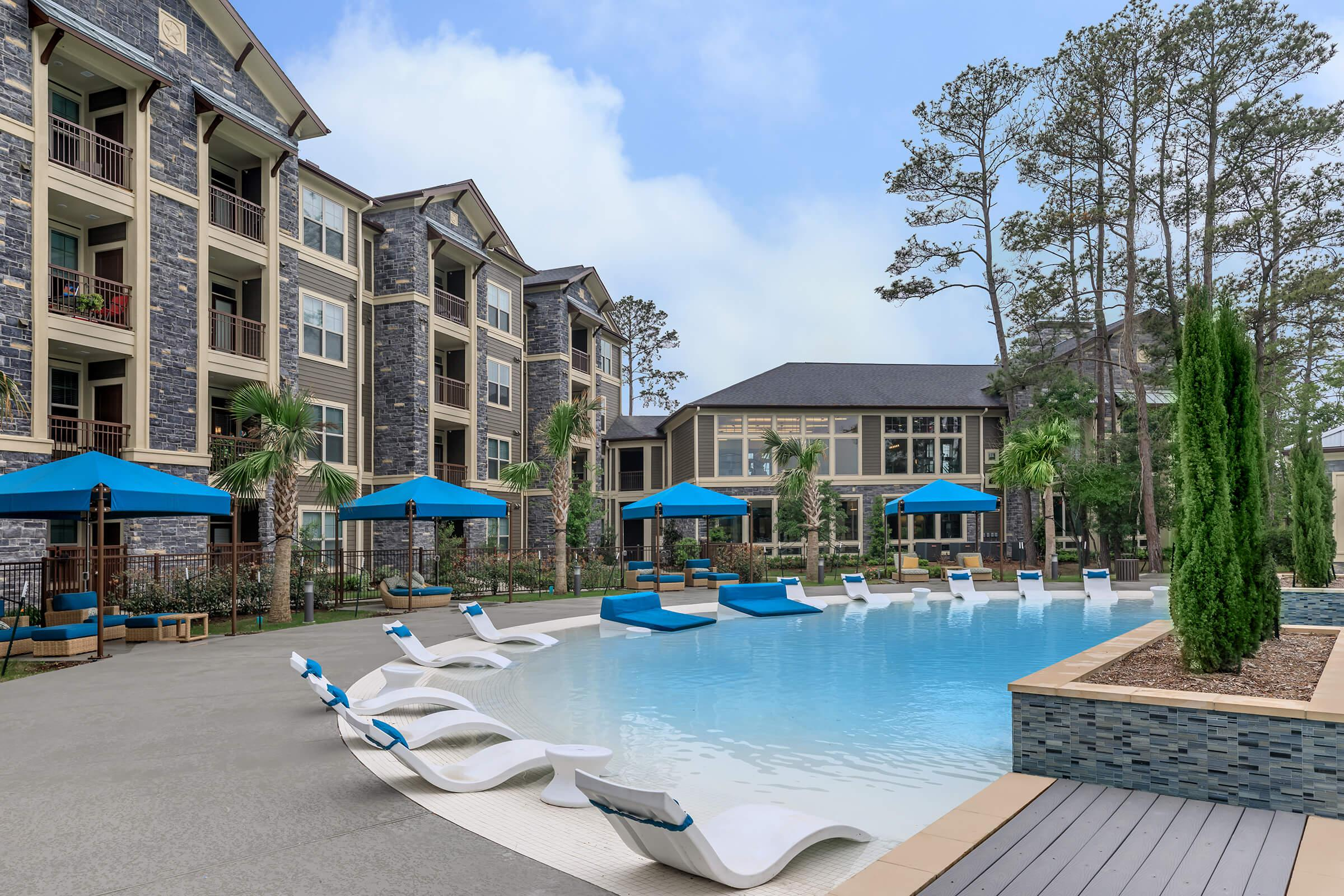 Beach entry pool with sunning area. Cabanas and Lounge chairs surrounding the pool.