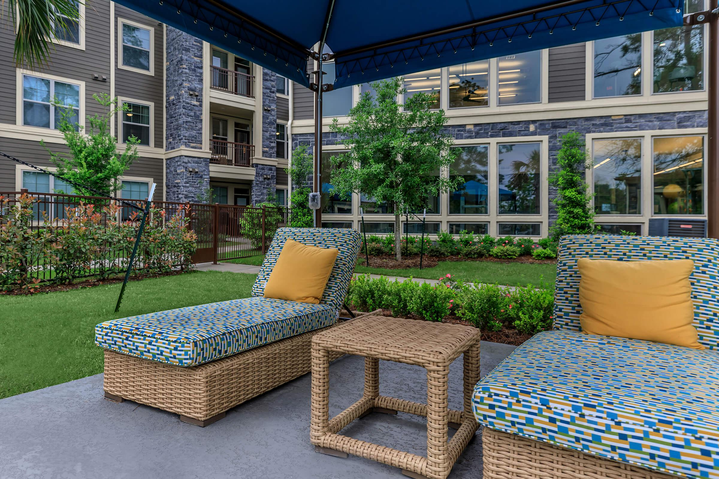 Cabana seating area with two padded loungers and green landscaping backdrop.