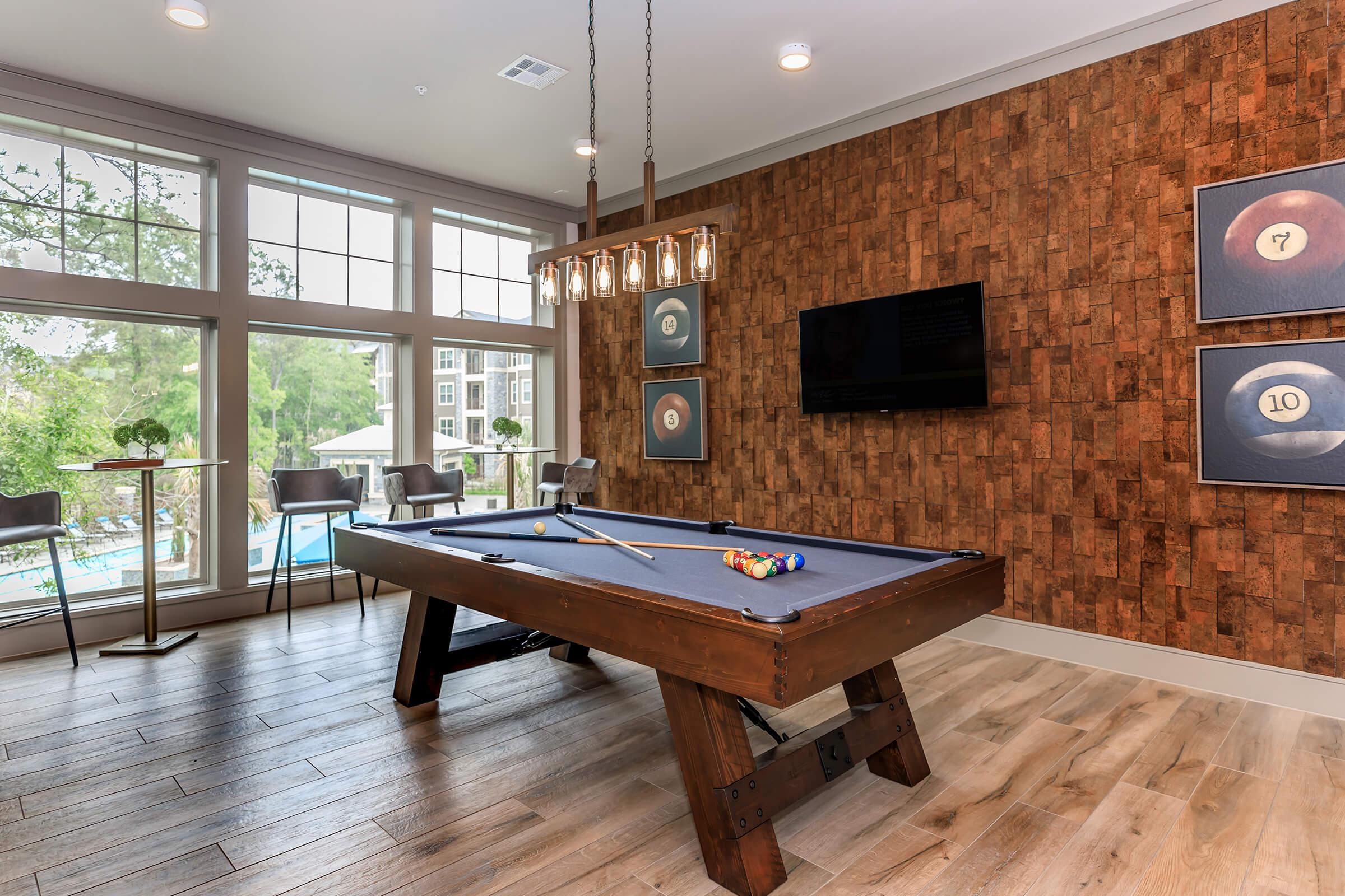 Billiards area of our upscale clubhouse with large windows and seating.