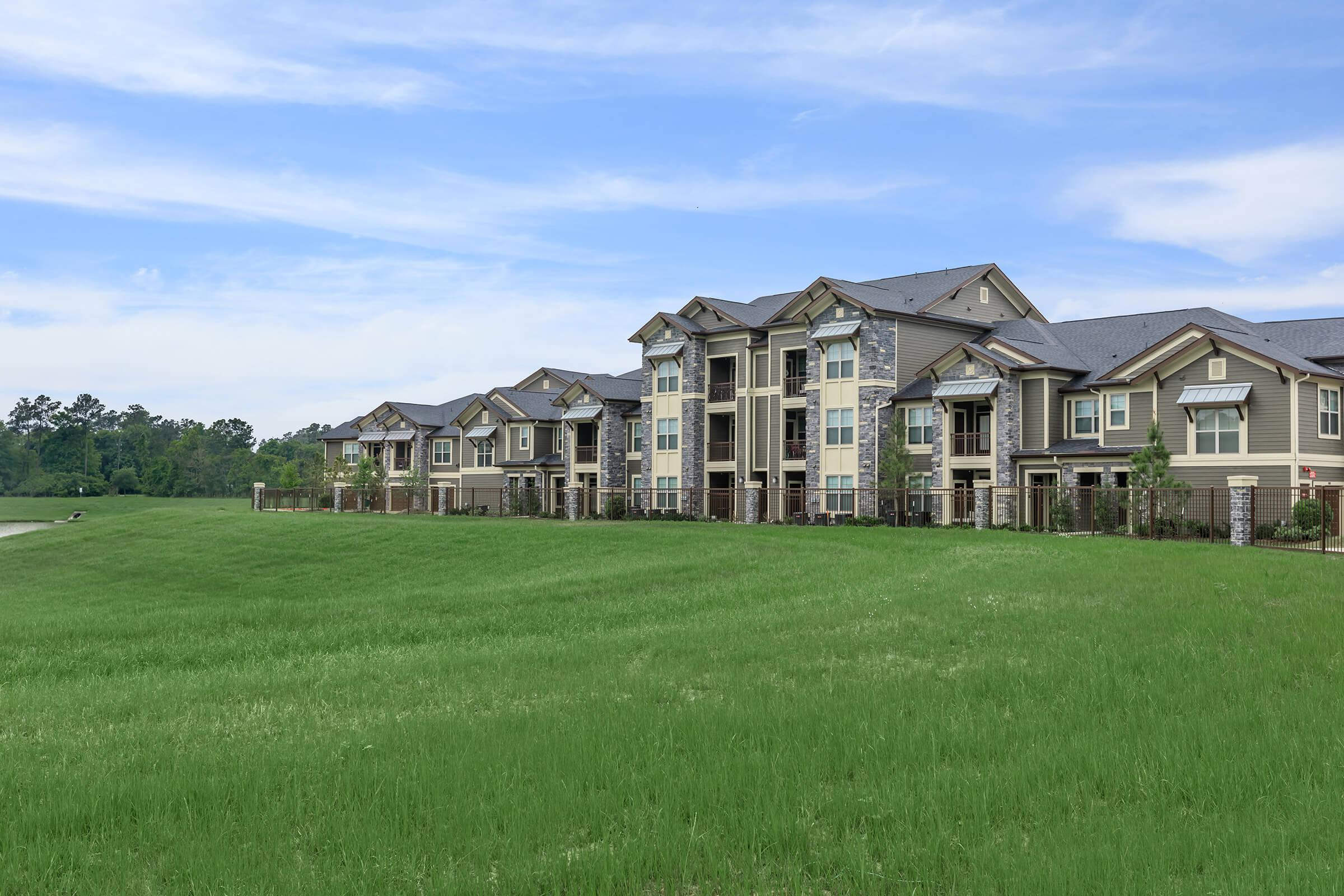 Open green grass of the golf course with Park at Tour 18 luxury apartment community.