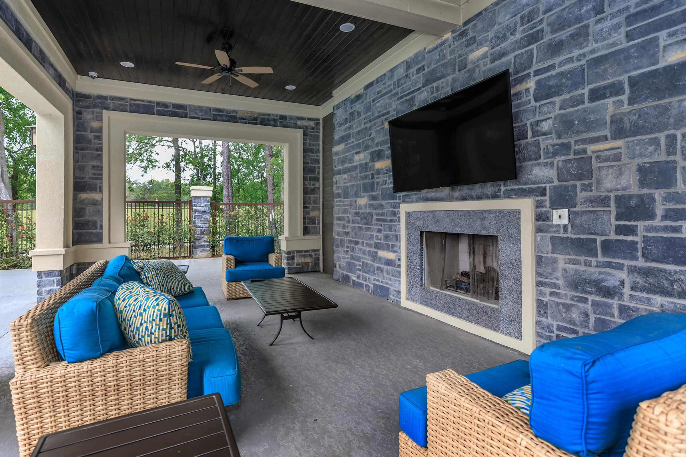 Outdoor lounge with fireplace, tv, and plush blue cushions on wicker seating.