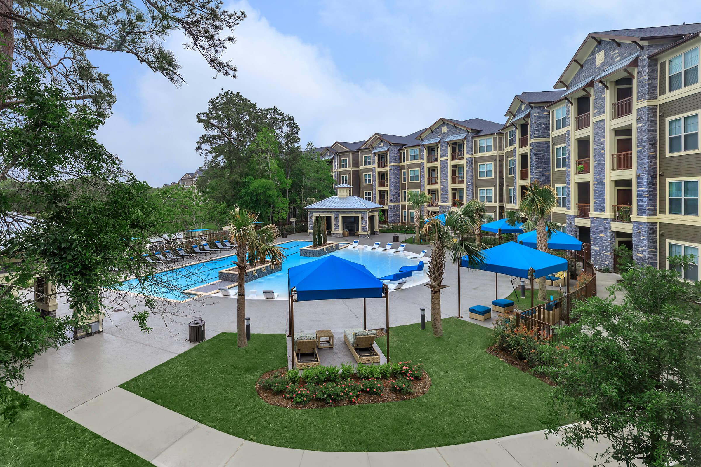 View of the pool area with cabanas, landscaping, and brand new apartment community.