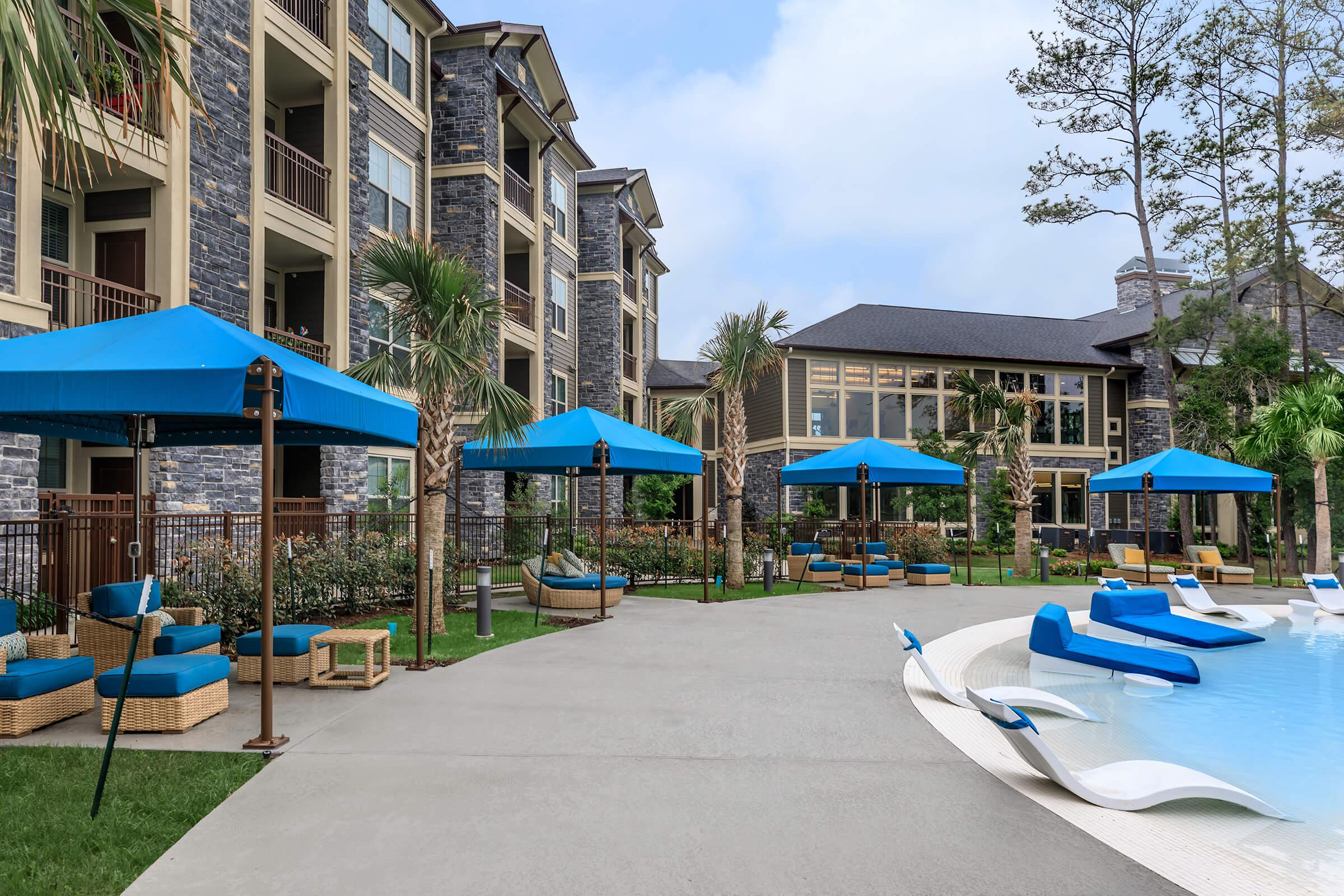 Cabanas in blue surrounding the beach entry area of our resort-style pool.