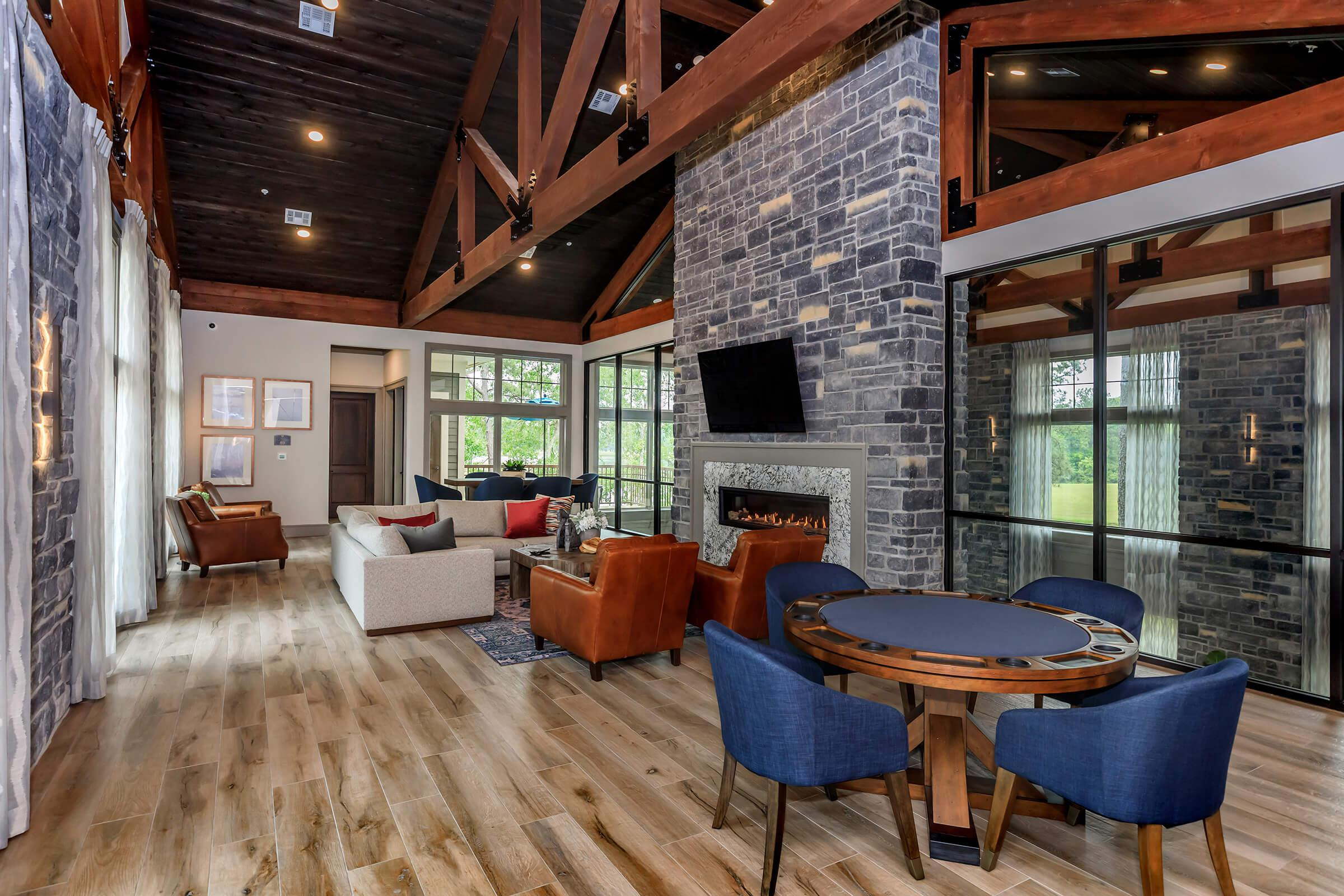 Upscale resident lounge showing multiple seating areas, TX, fireplace, and wood floors.