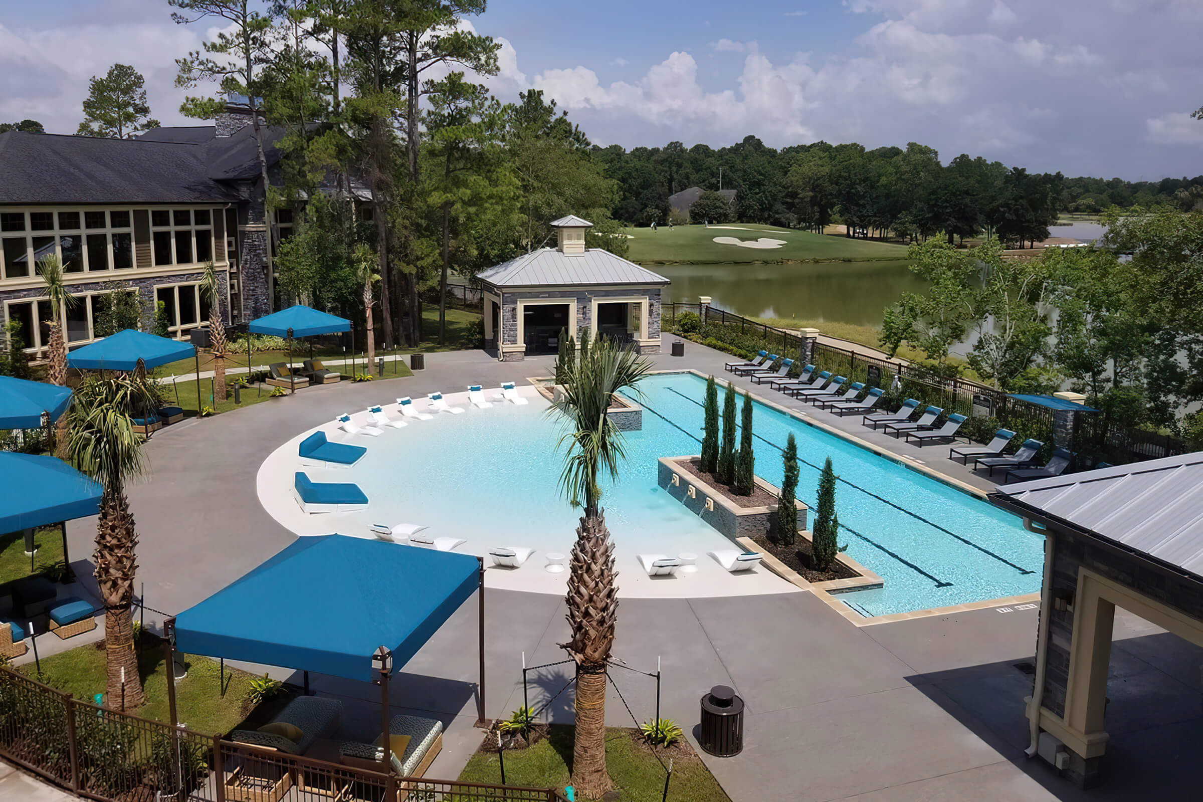 Cabanas around pool with shallow half cirlcle connected to deeper rectangular pool. Golf course view