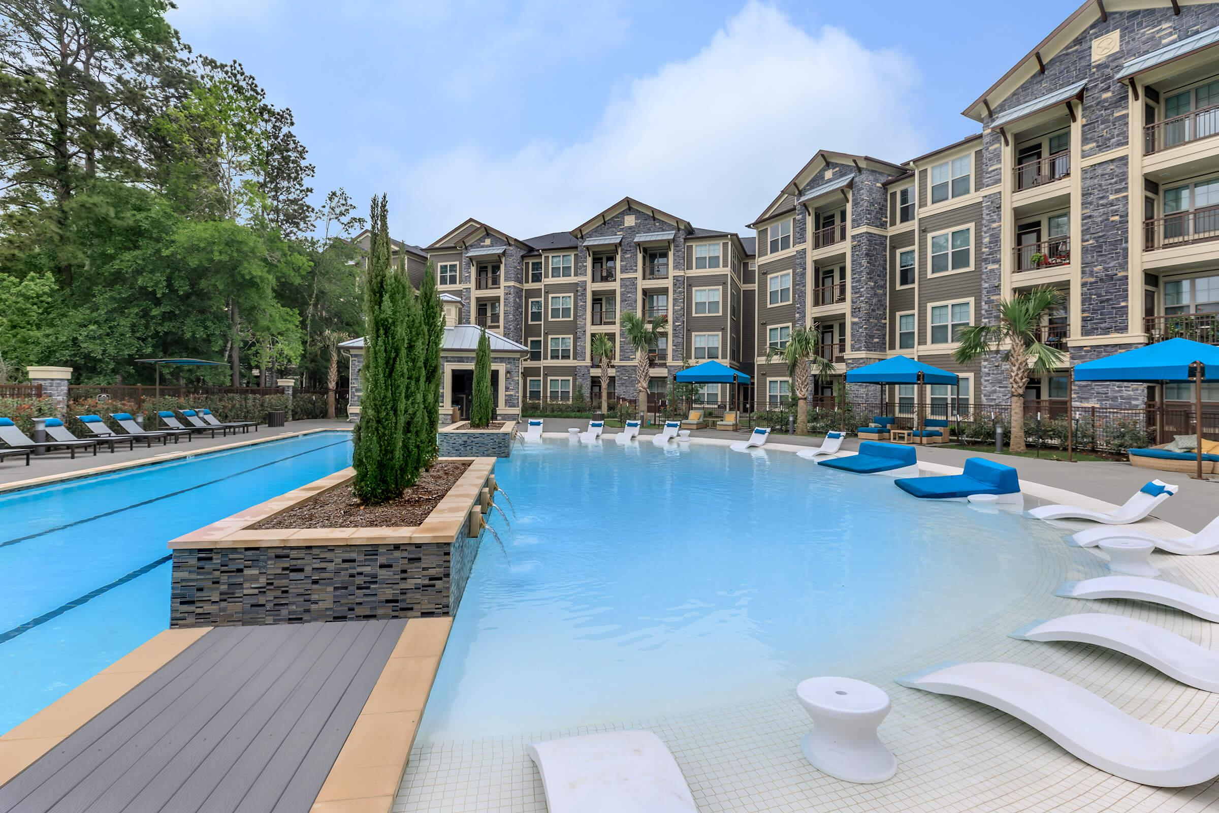 Resort-style pool with beach entry, water loungers, and apartment building to the right.