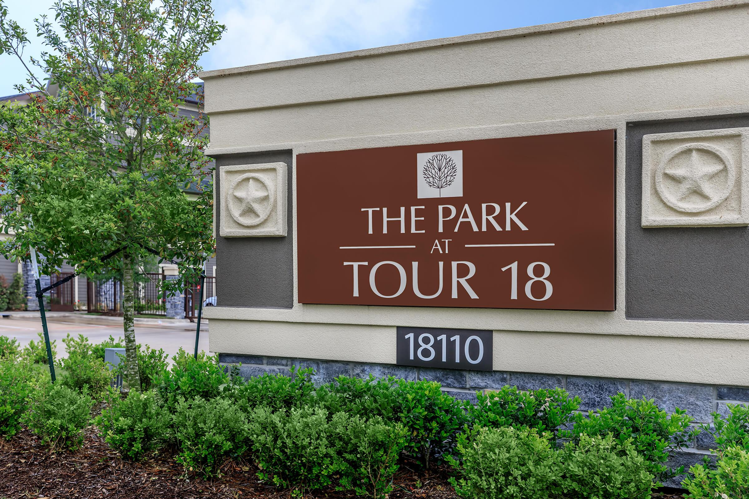 Park at Tour 18 monument sign in red with landscaping surrounding.