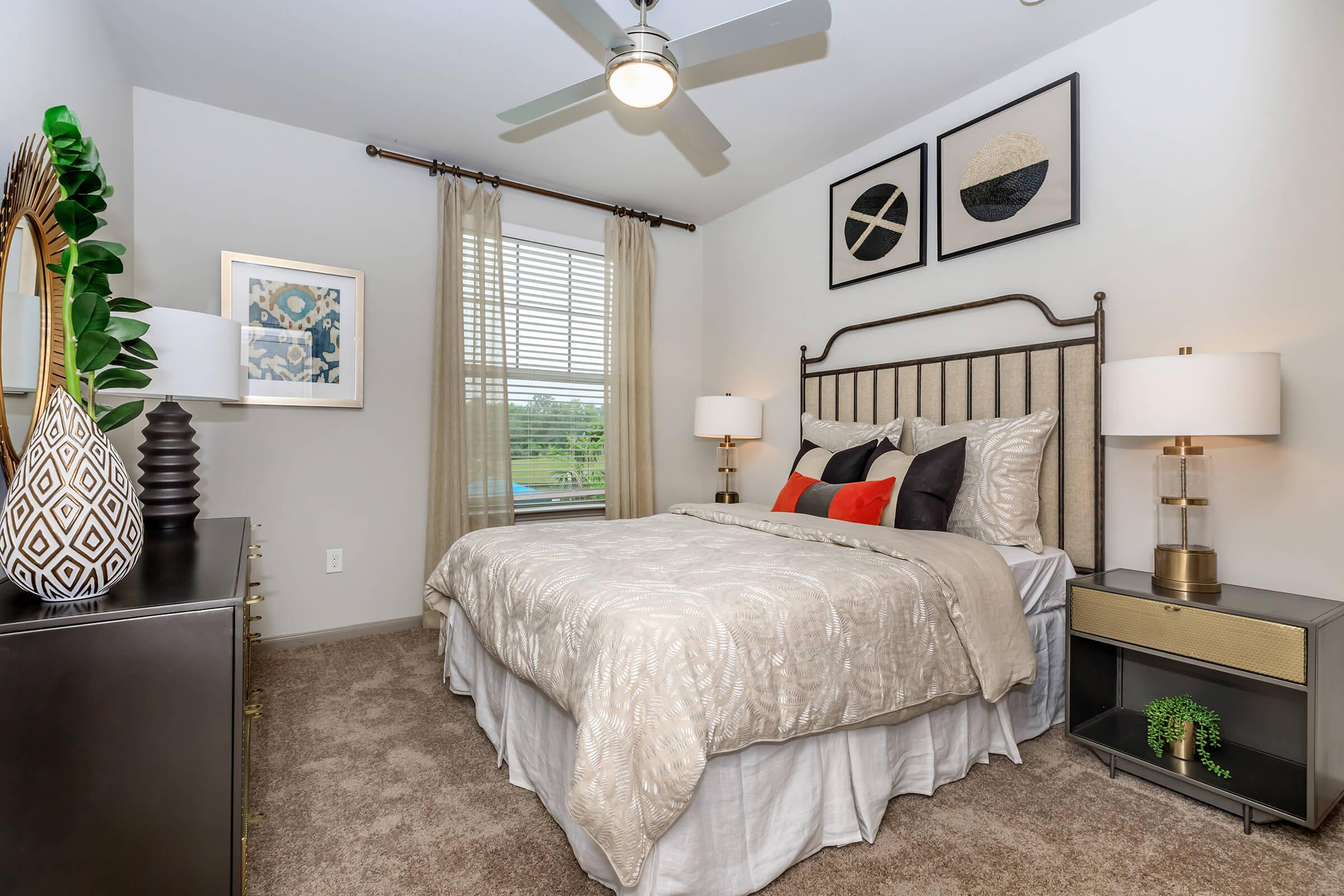 Serene bedroom staged with furniture and open window view of golf course.