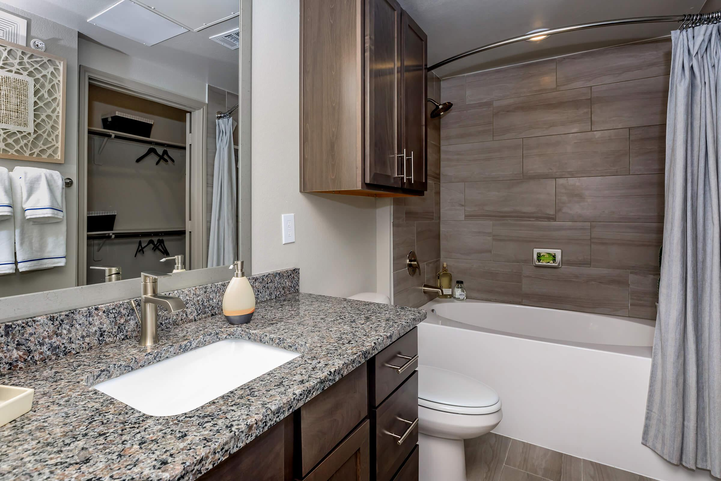 Modern bathroom in brand new apartment. Granite counters, tub with surround, and large mirror.