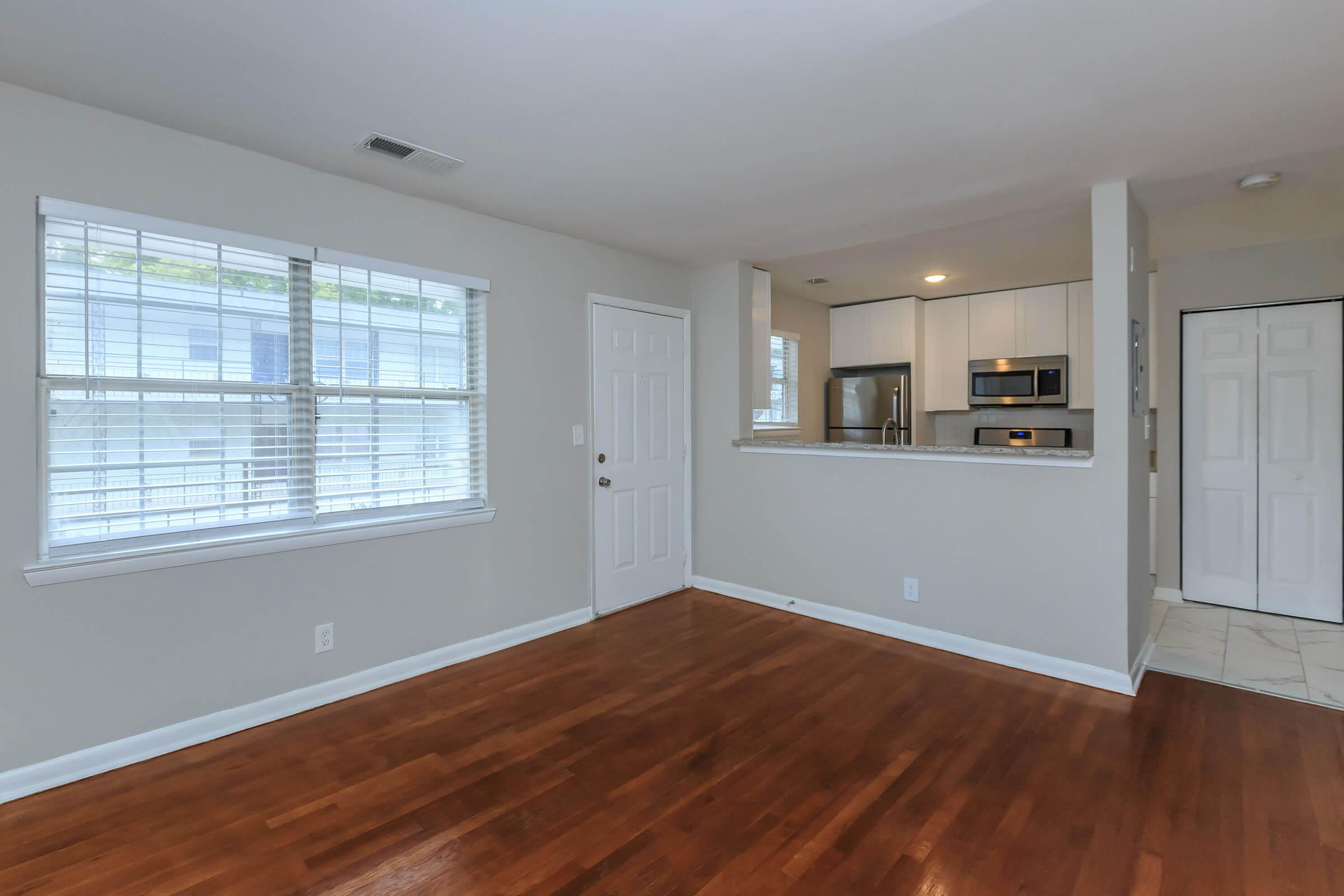 a room with hard wood floors and a large window