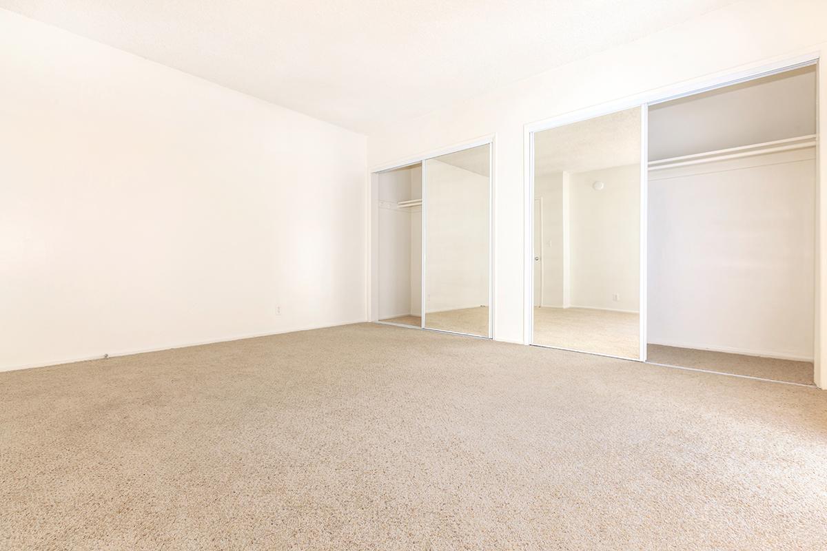Bedroom with open sliding mirror glass closet doors