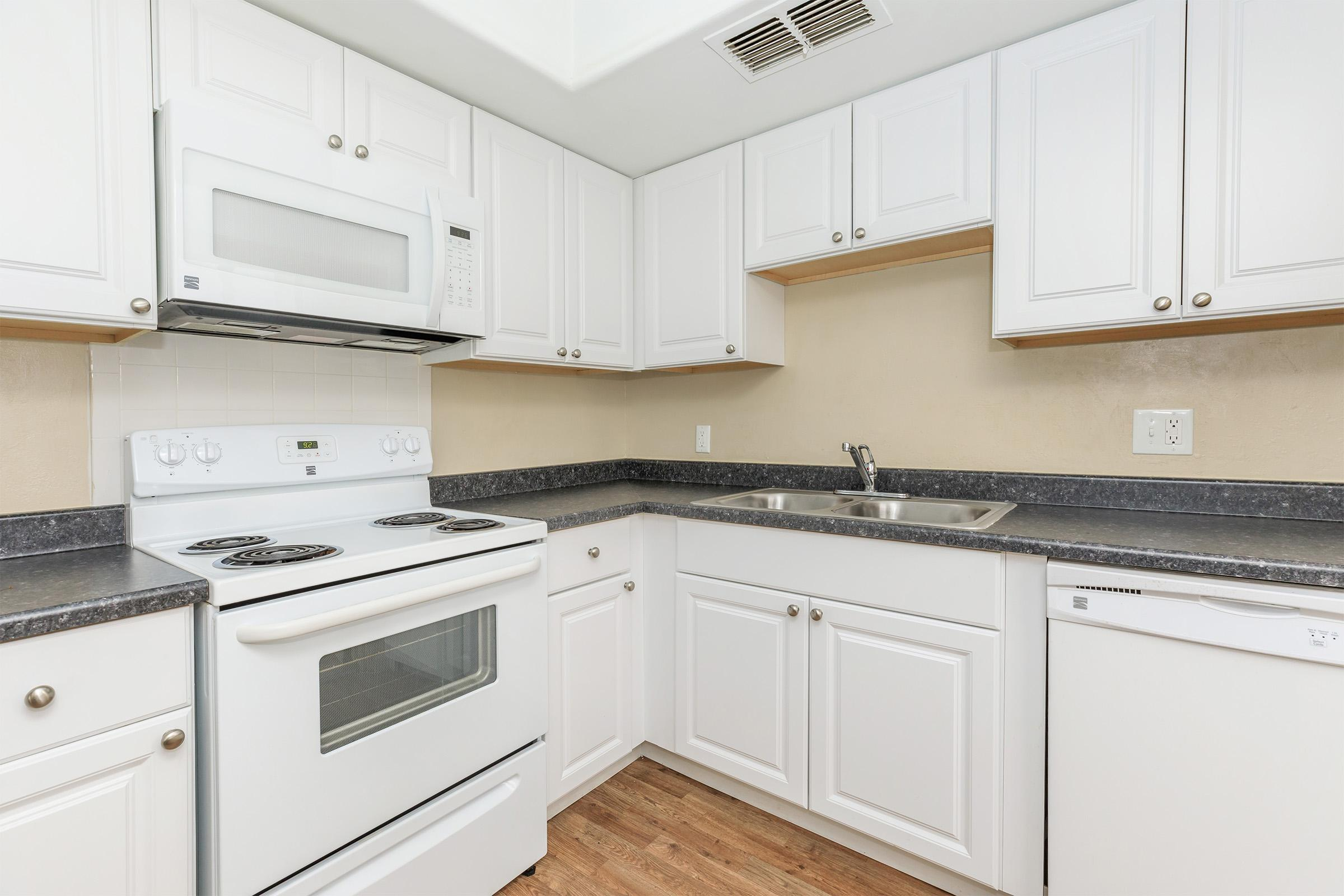 a white stove top oven sitting inside of a kitchen