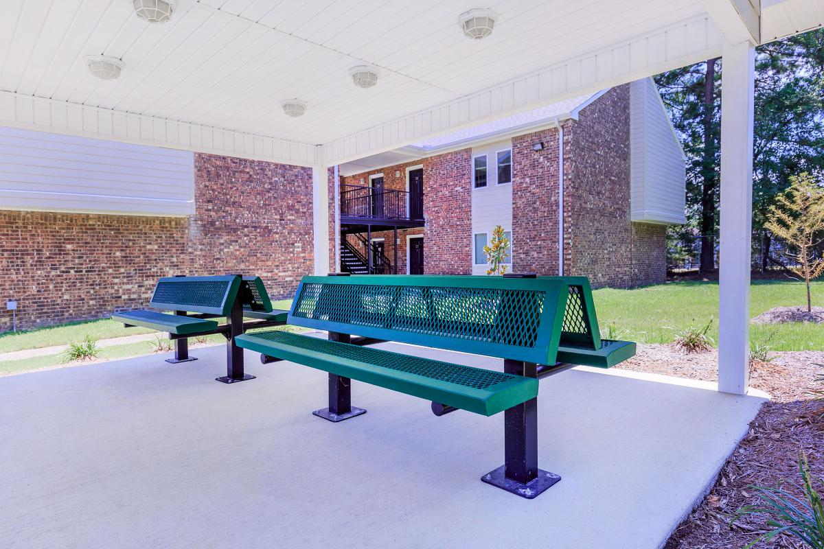 an empty park bench sitting in front of a building