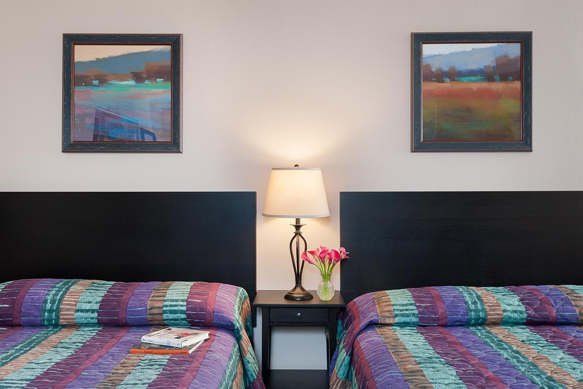 a colorful living room with a bed and a painting