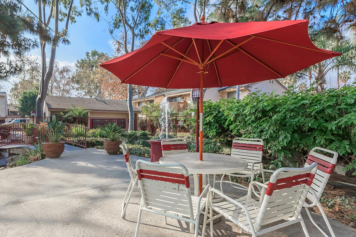 A table and chairs with red umbrella