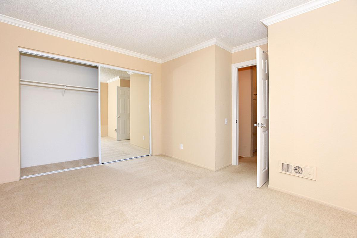 Unfurnished bedroom with open sliding mirror glass closet doors