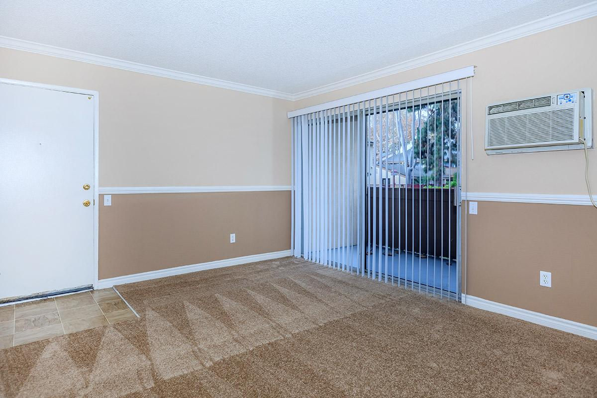 Carpeted living room with sliding glass doors to patio