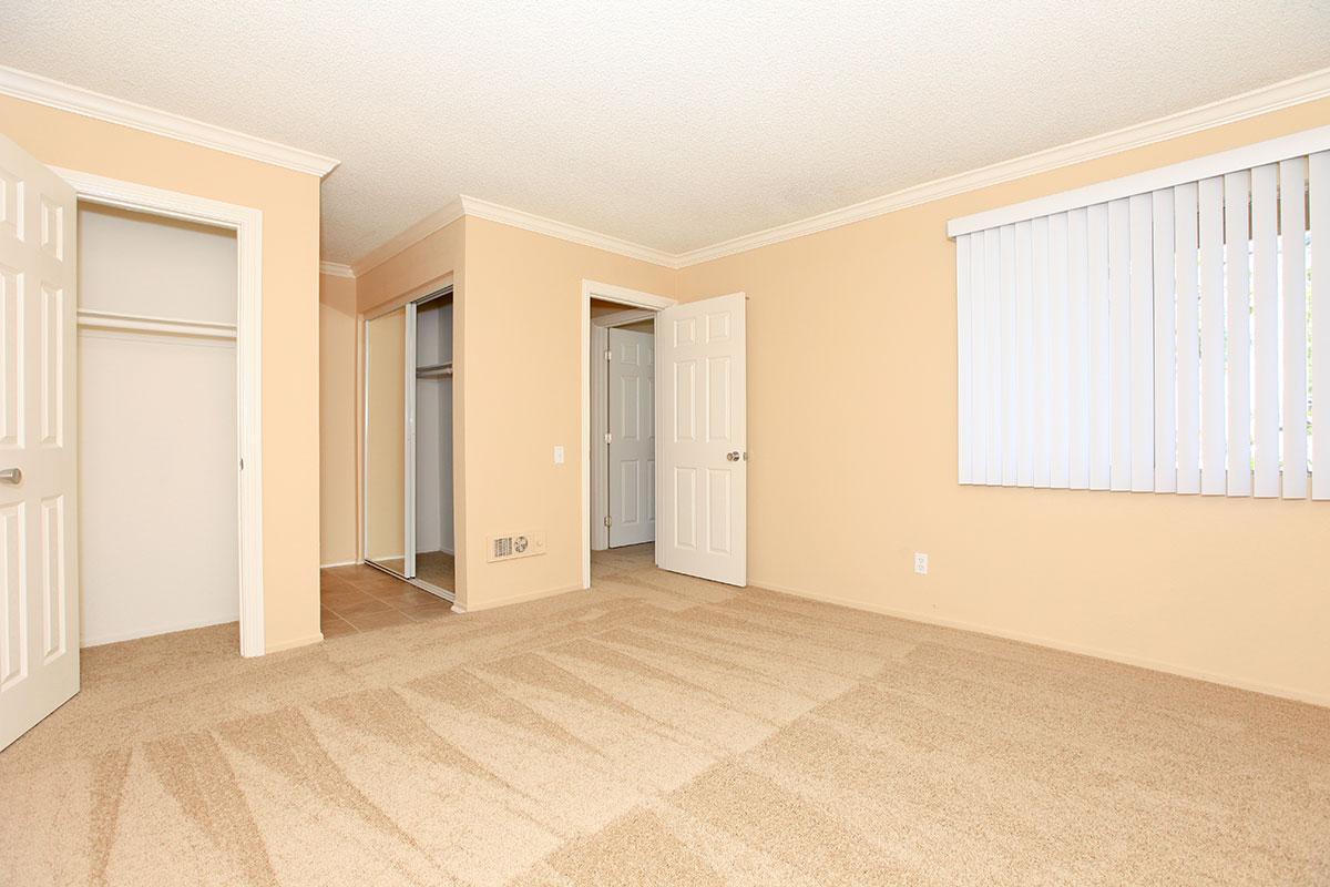 Vacant bedroom with open closet doors