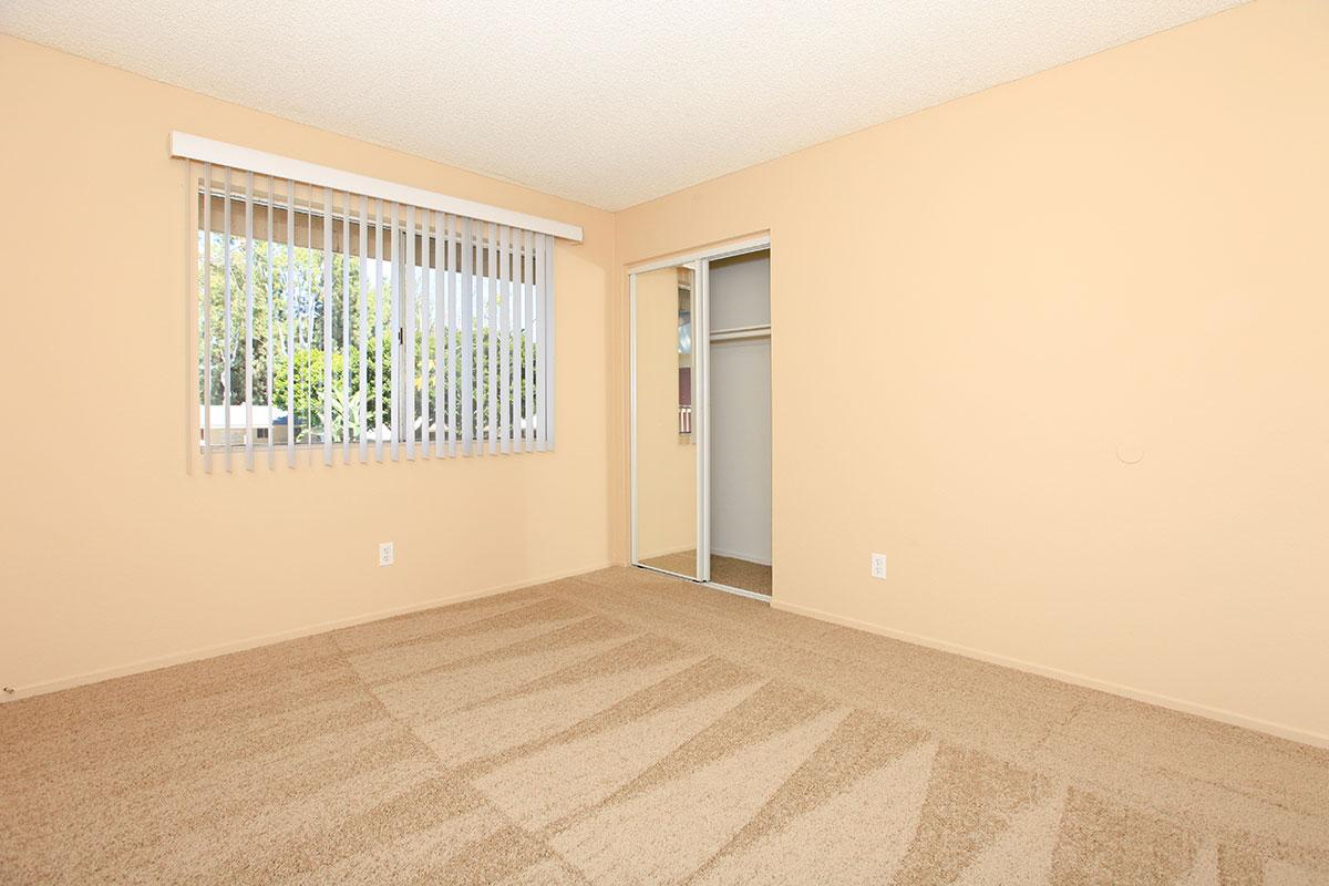 Vacant carpeted bedroom with open sliding mirror glass closet doors