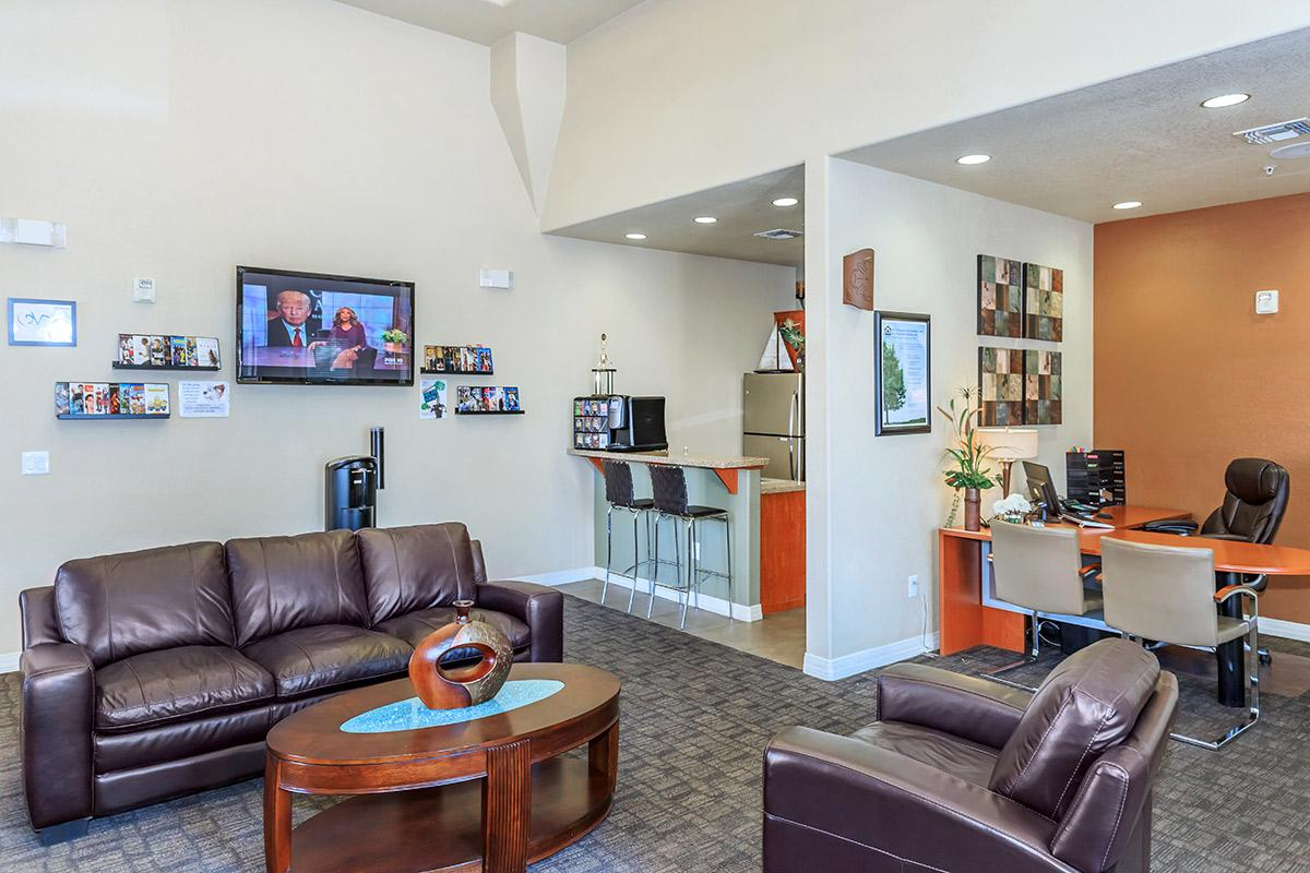 a brown leather couch in a living room filled with furniture and a tv