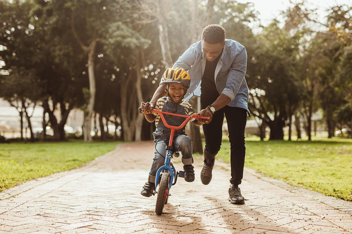 a young man riding a bike down a dirt road