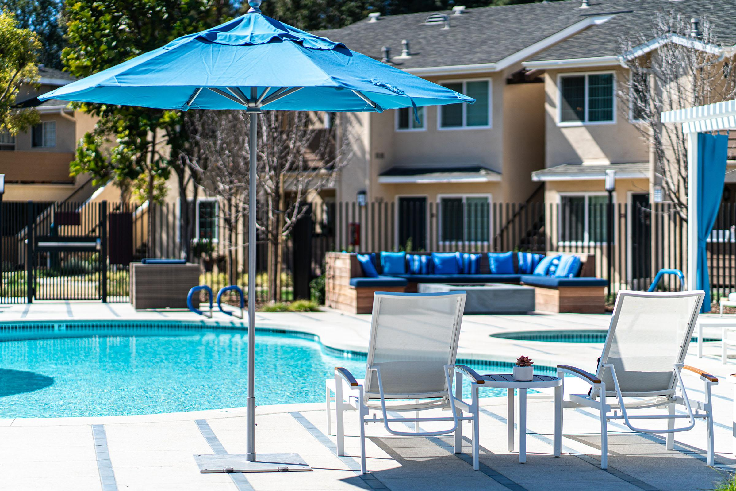 a group of lawn chairs sitting on a pool table with a blue umbrella