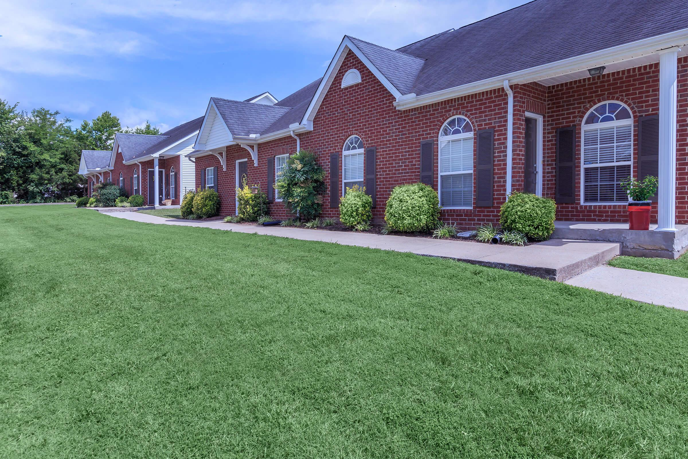 a large brick building with green grass in front of a house