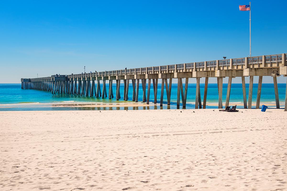 a beach with a pier in the water