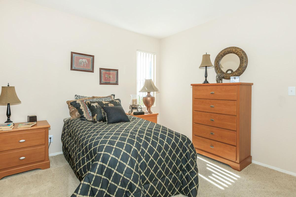 a bedroom filled with furniture and a lamp in a room