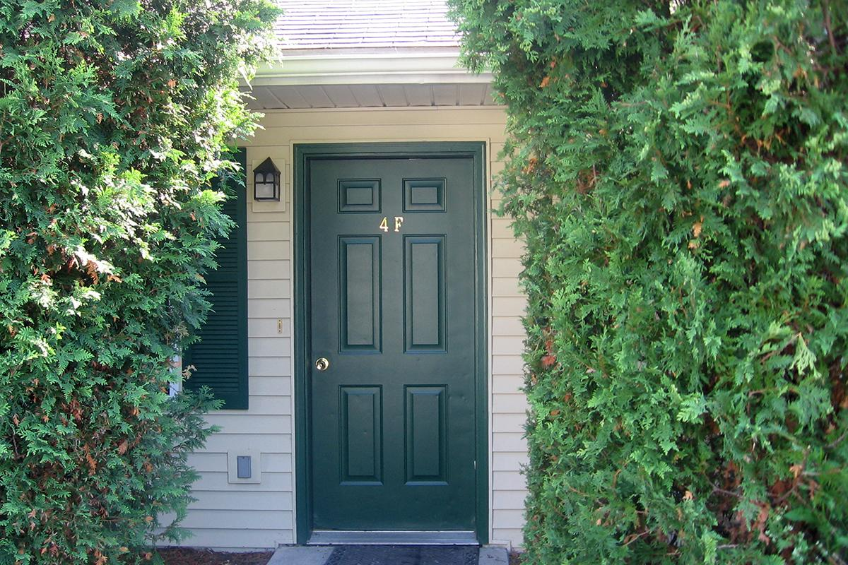 a house with bushes in front of a door