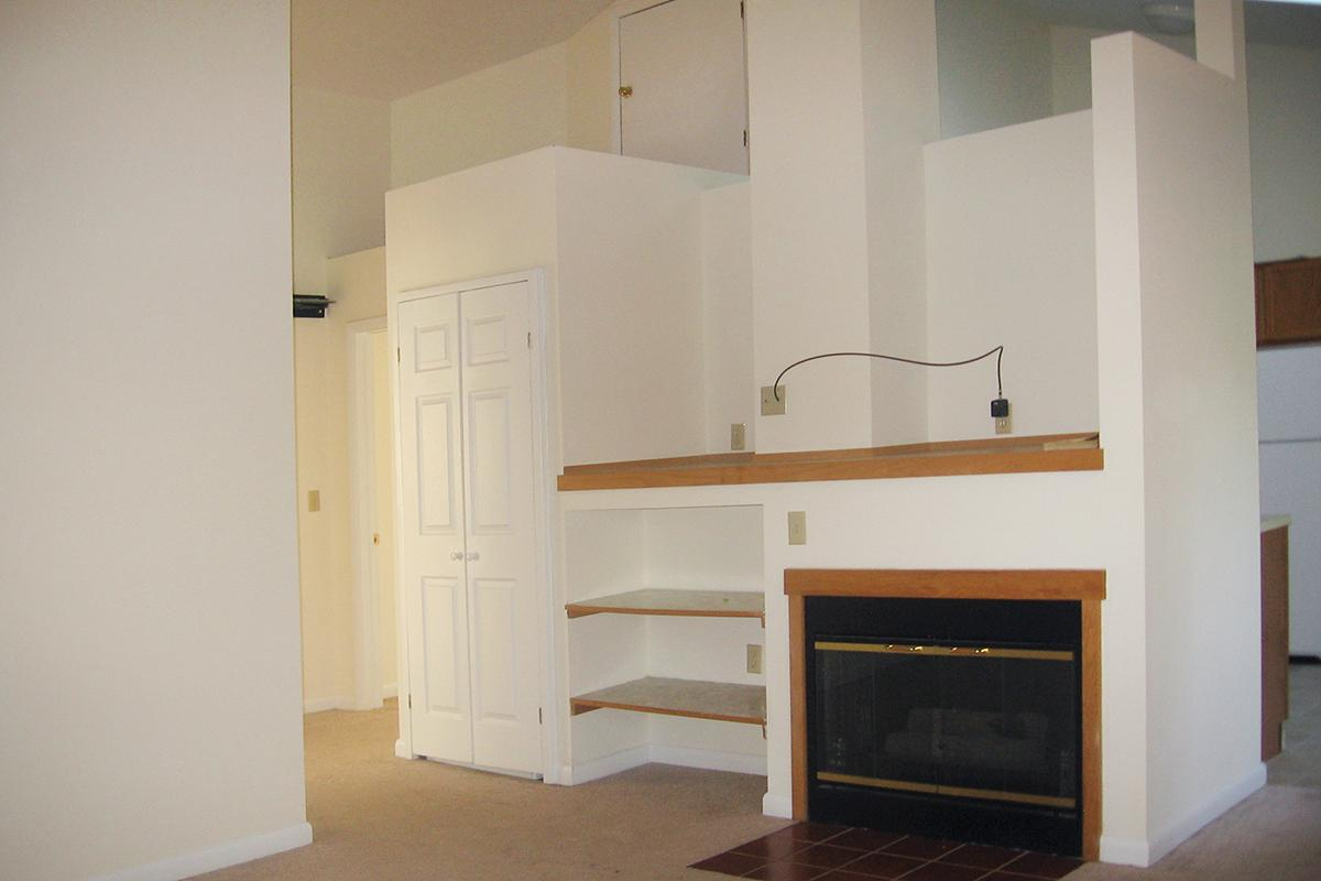 a kitchen with white cabinets and a fireplace