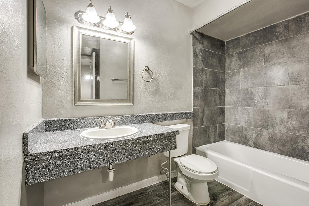 a large white tub sitting next to a sink and a mirror
