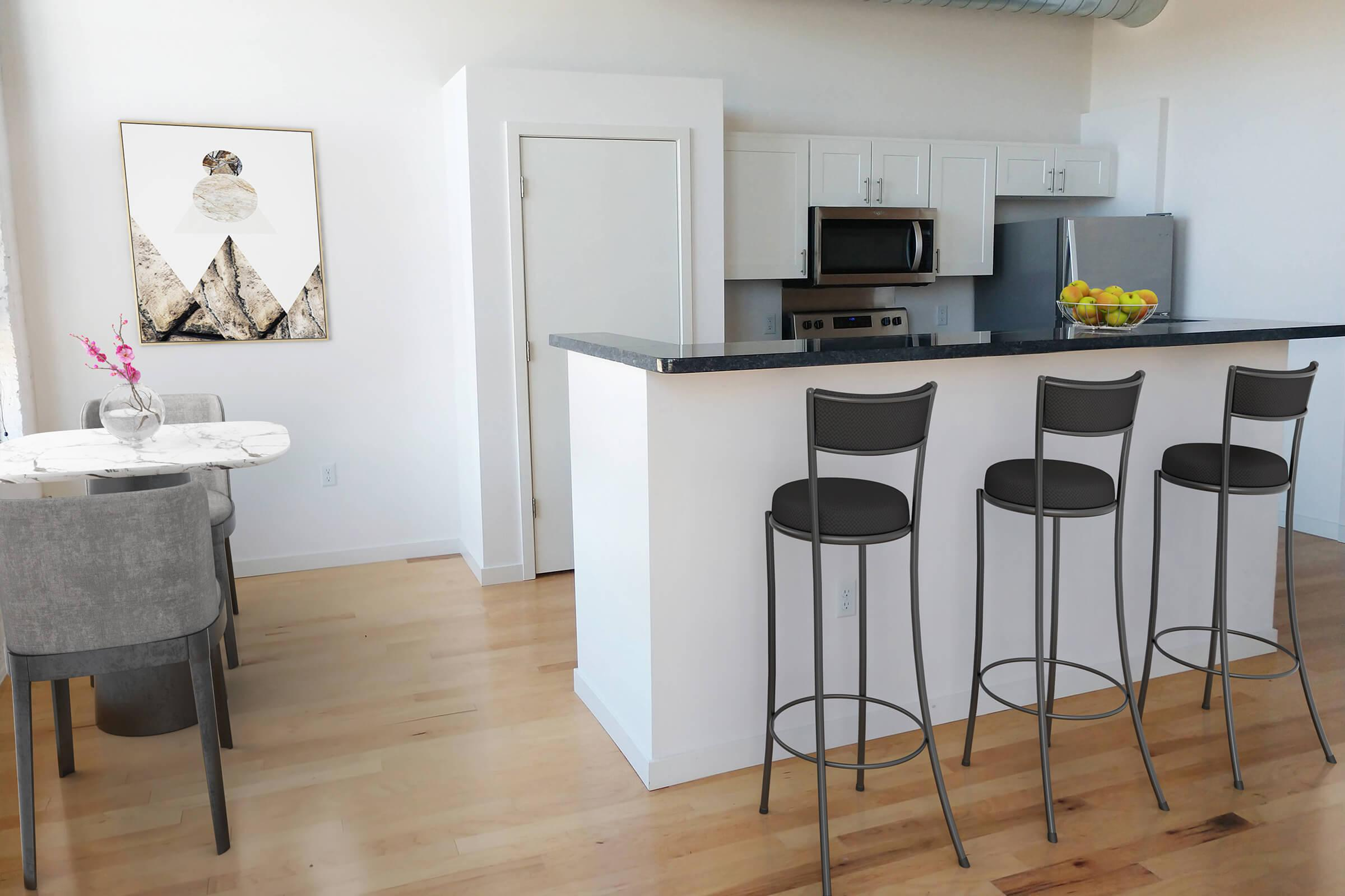 a kitchen with a table and a chair in a room