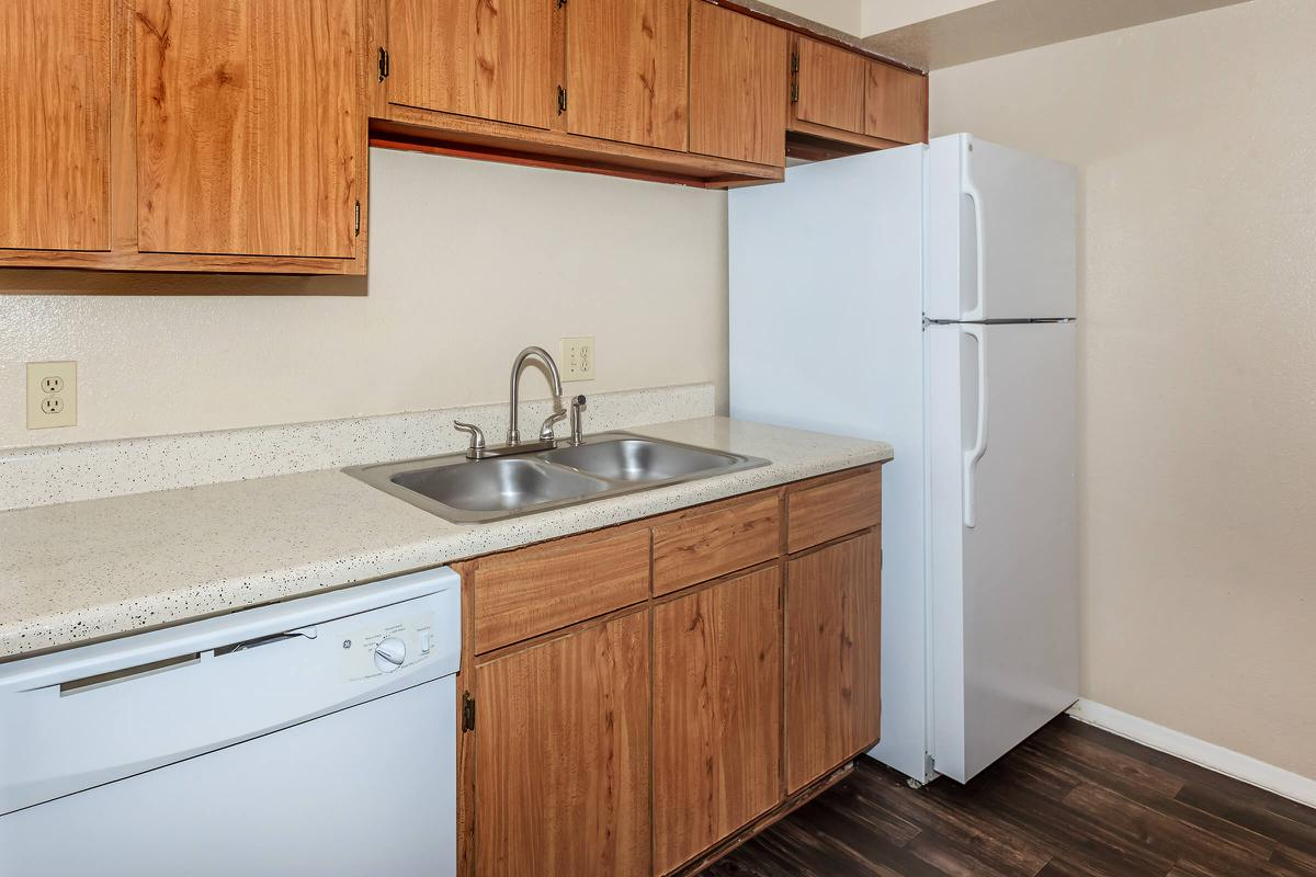 a kitchen with white appliances and wooden cabinets