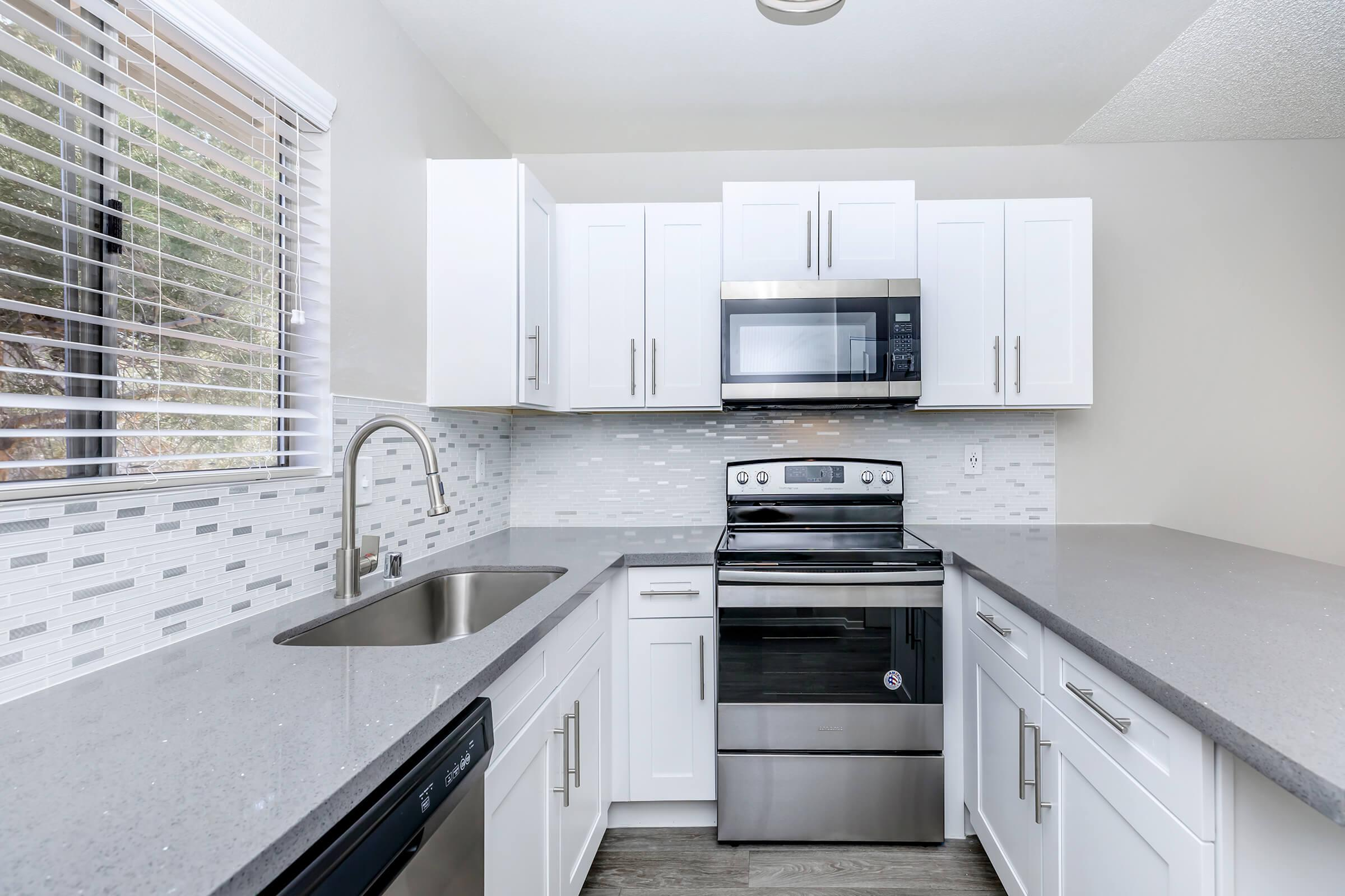 a kitchen with white cabinets and black counter