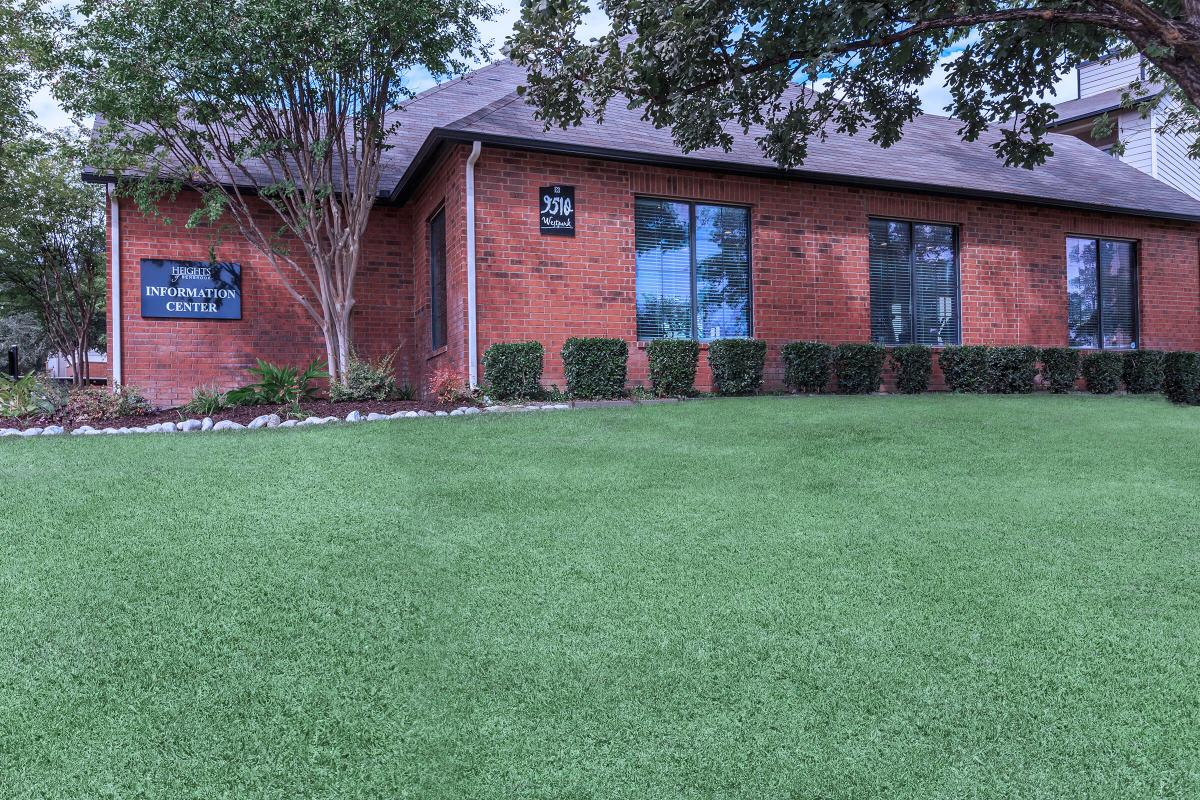 a house with a lawn in front of a brick building