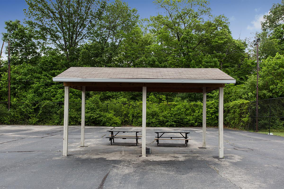 an empty park bench sitting in the middle of a road