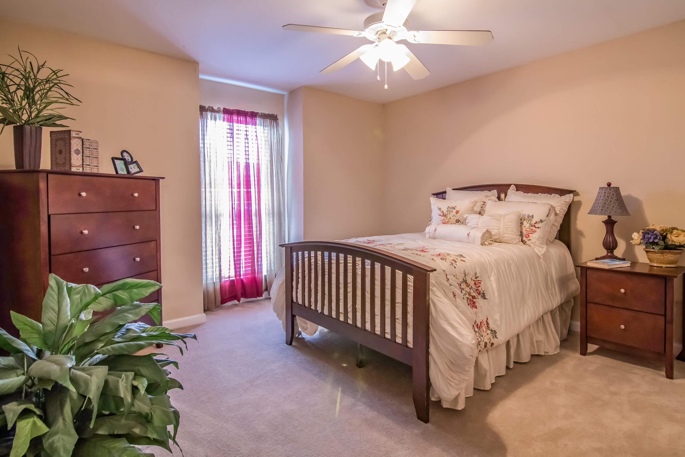 a bedroom with a bed and furniture in a room