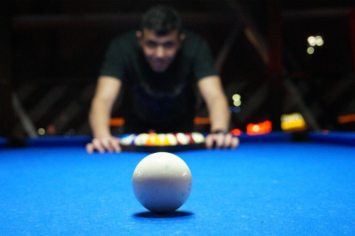 a person sitting at a table with a blue ball