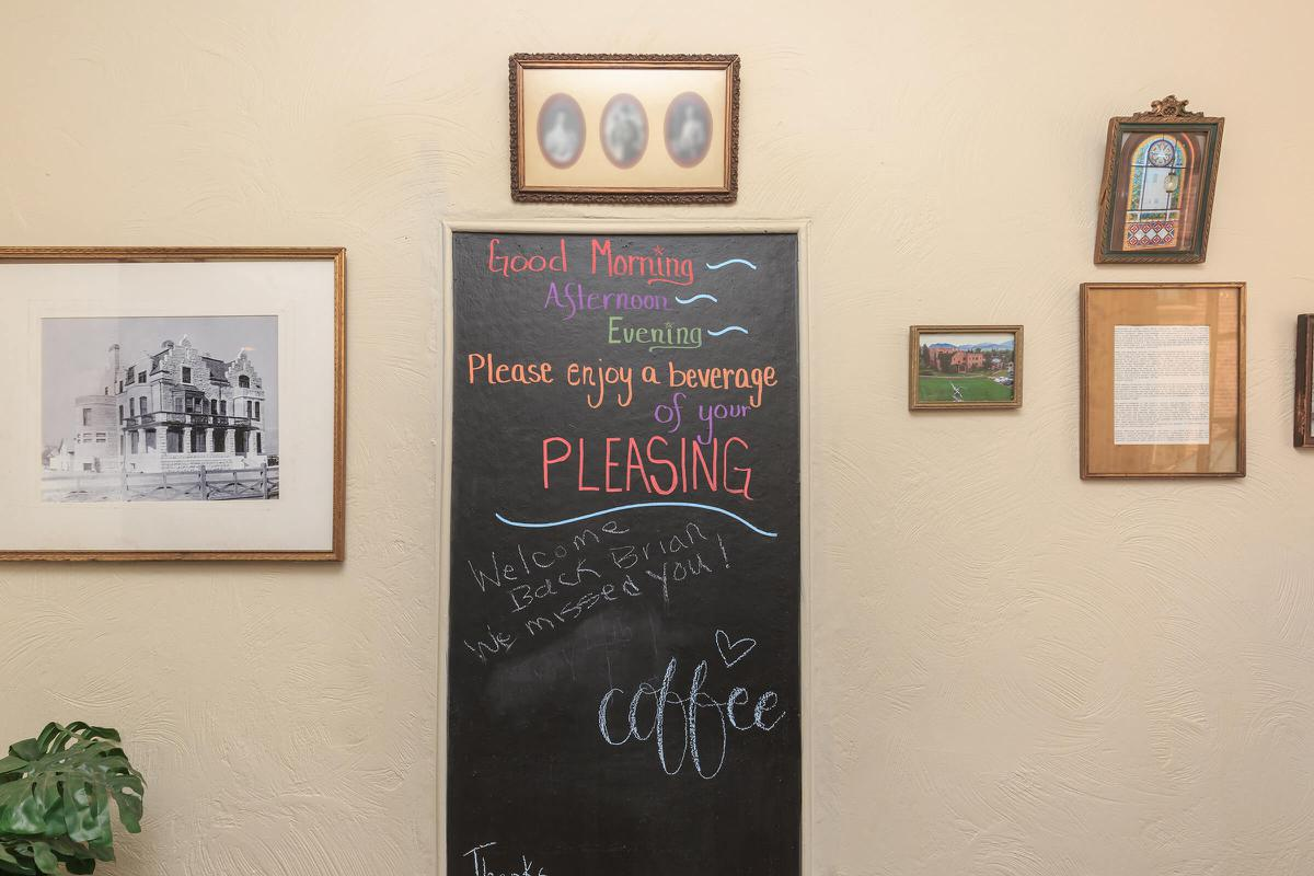 a blackboard sign next to a painting