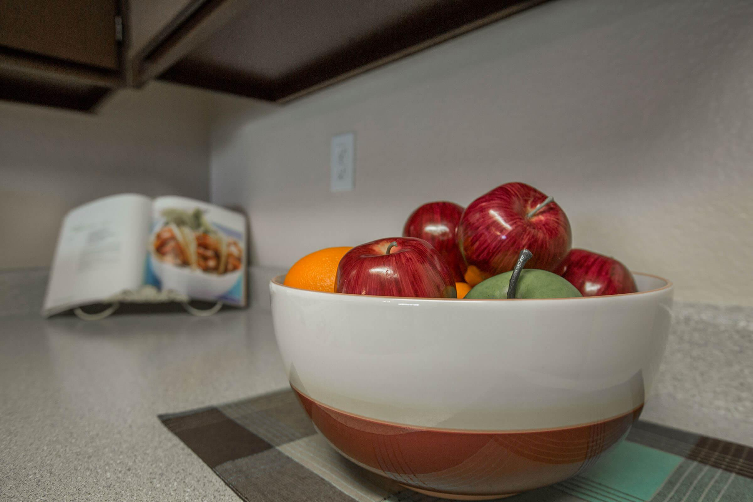 a bowl of fruit sitting on a table
