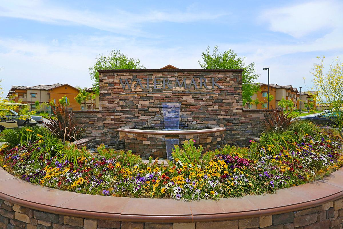 a close up of a flower garden in front of a brick building