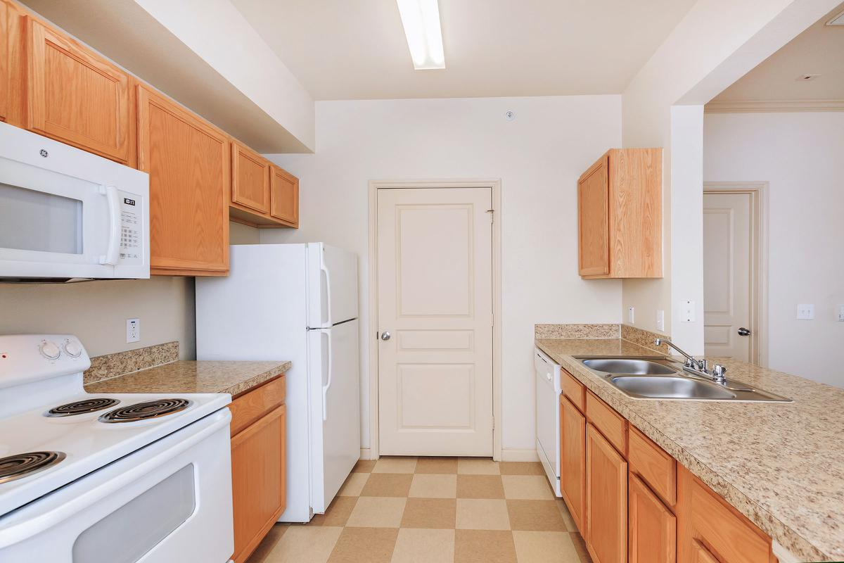 a kitchen with a stove a sink and a microwave oven above a refrigerator
