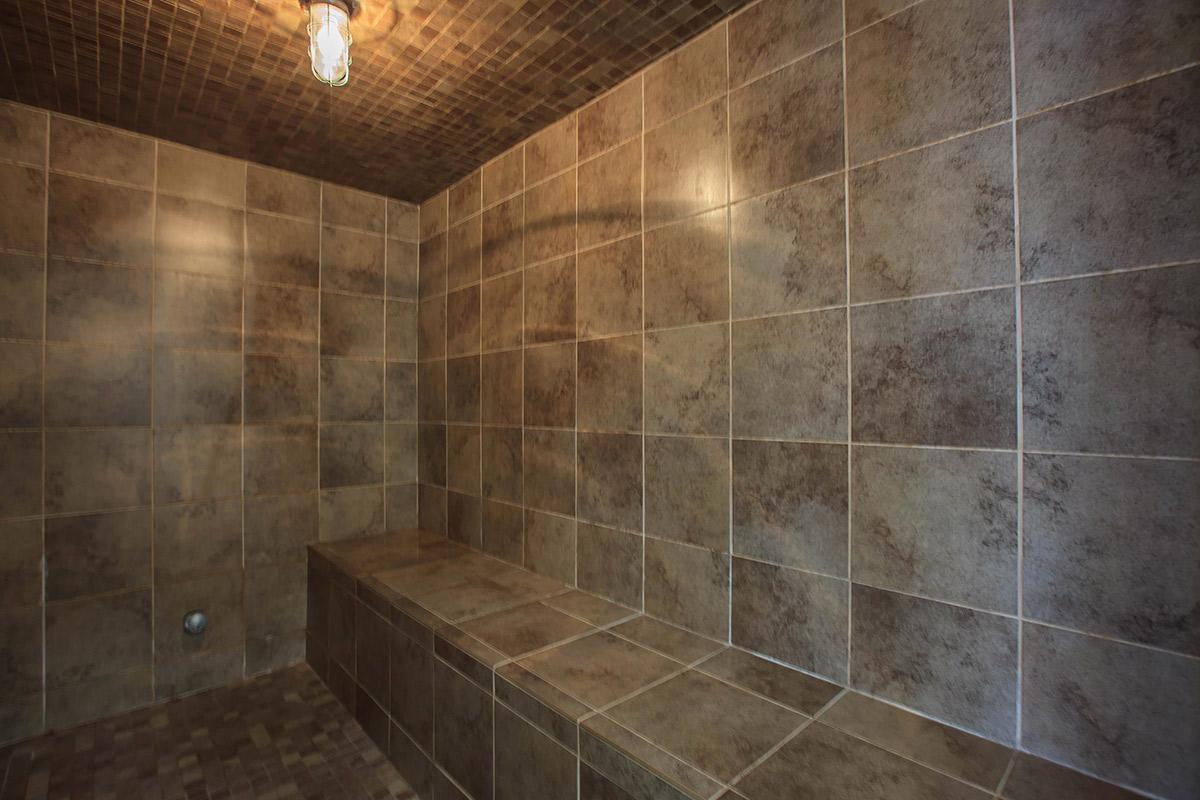 a brown tiled floor next to a shower