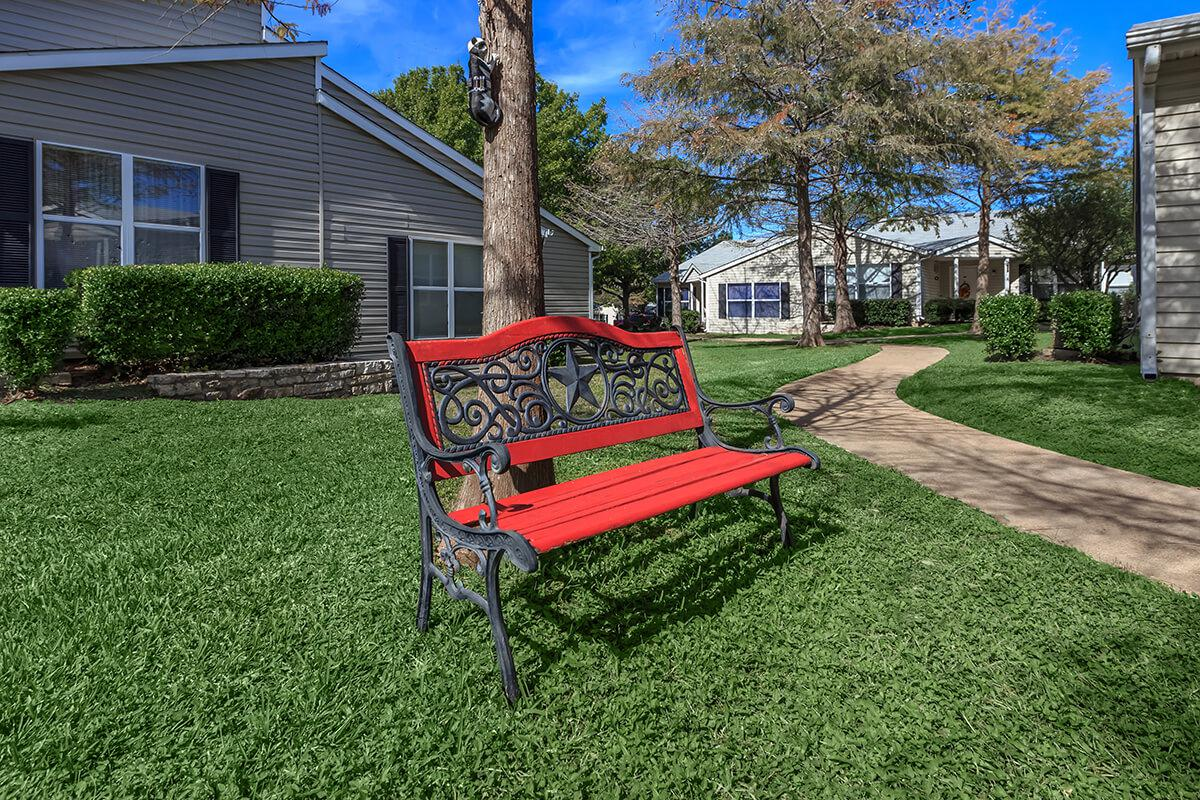 a couple of lawn chairs sitting on top of a grass covered field