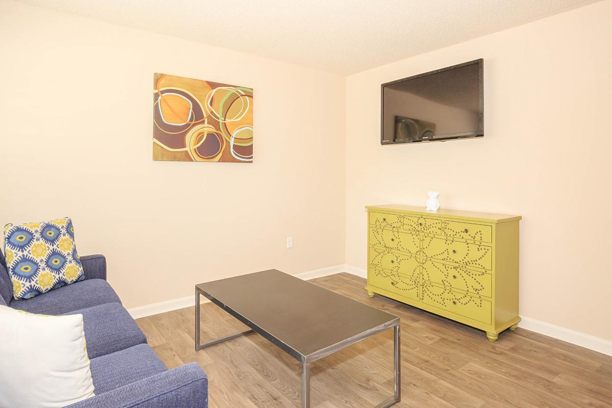 a living room filled with furniture and a painting on the wall