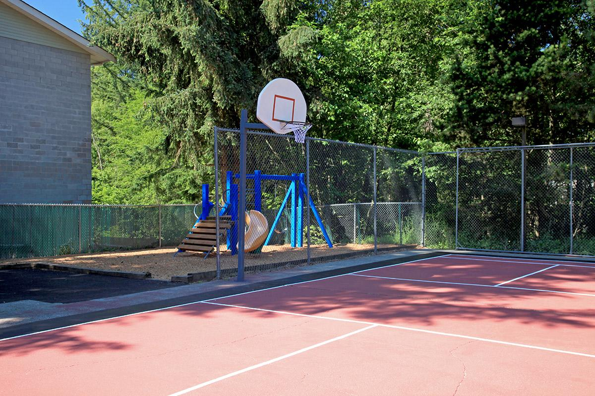 a person hitting a ball with a racket on a basketball court